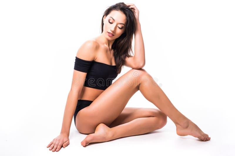Färdig och sportig flicka i svart underkläder på golvet Härlig och sund kvinna som poserar över isolerad vit bakgrund Sport passf royaltyfri foto