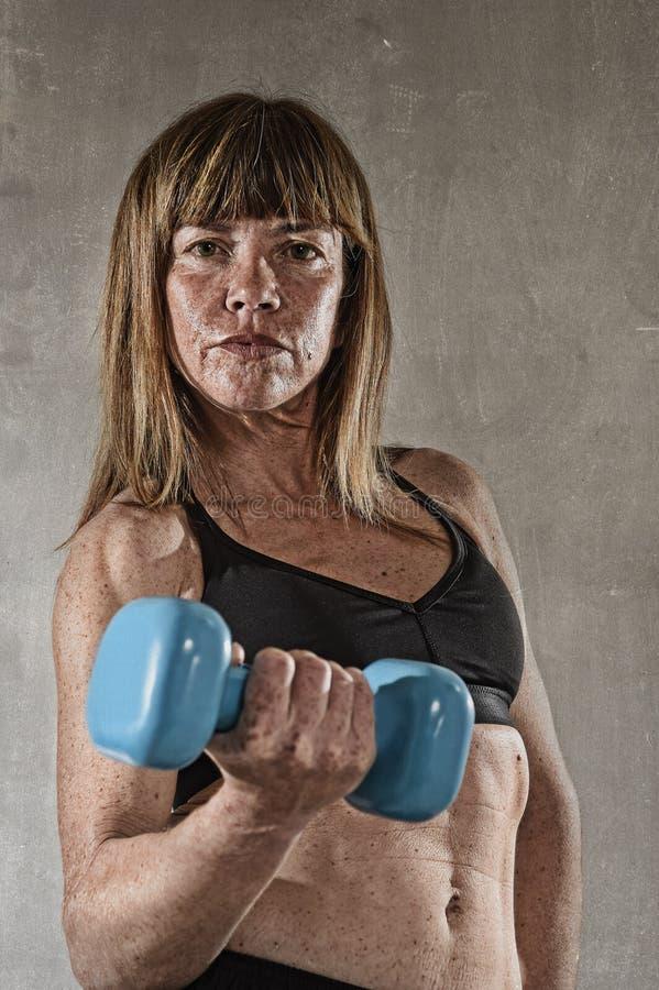 Färdig och stark vikt för sportkvinnainnehav på hennes posera för hand som är utmanande i kall inställning royaltyfri bild