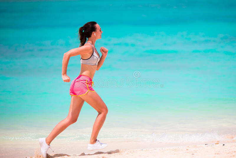 Färdig spring för ung kvinna längs den tropiska stranden i hennes sportswear royaltyfria foton