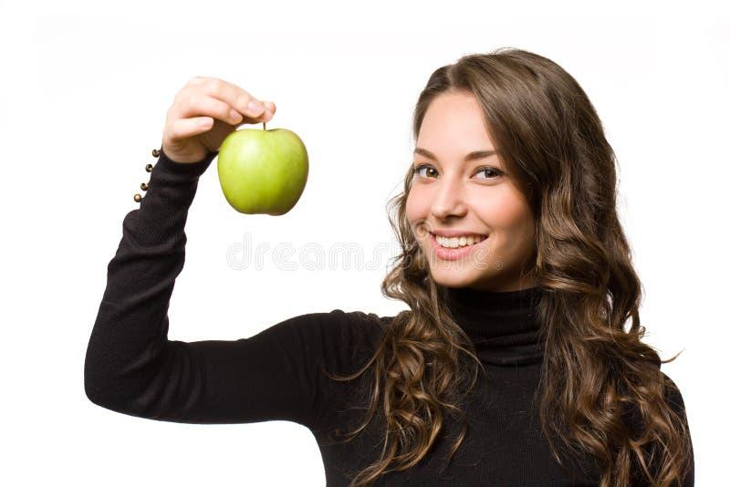 Färdig ung brunett med det gröna äpplet. arkivfoton