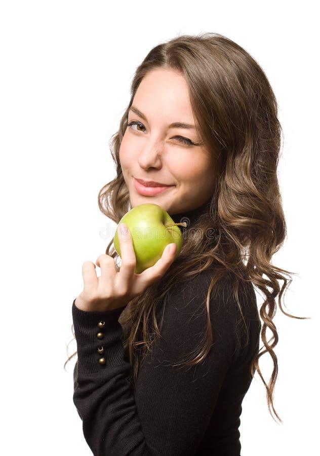 Färdig ung brunett med det gröna äpplet. royaltyfria bilder