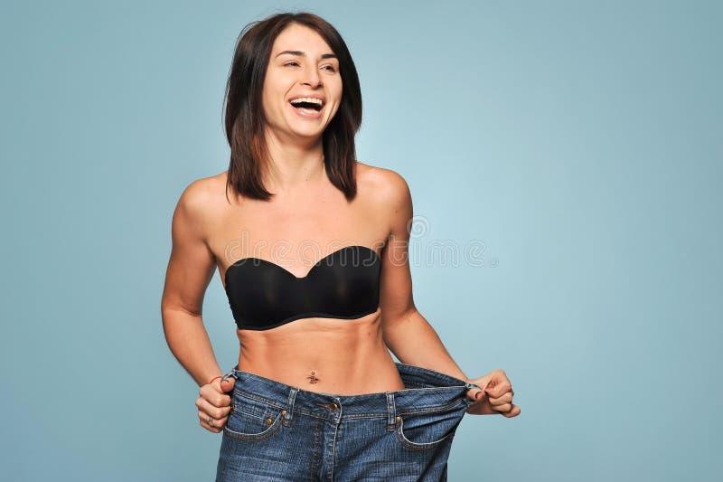 Färdig ung kvinna i lös jeans arkivfoto