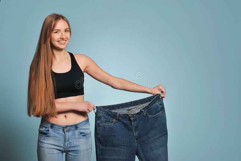 Färdig ung kvinna i lös jeans royaltyfria bilder