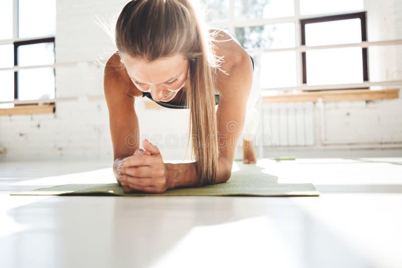 Färdig ung kvinna som övar i den vita inre idrottshallen arkivbild