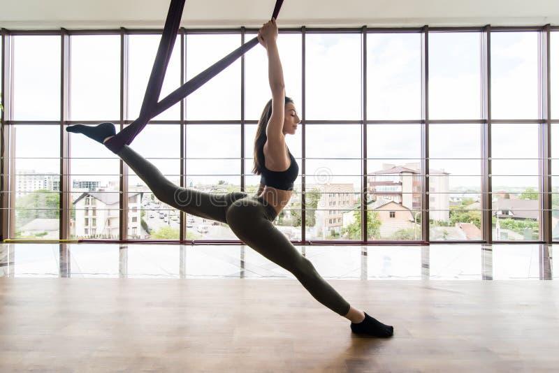 Färdig ung kvinna som gör asanaen för gravitationflugayoga som sträcker övningar i utbildande vit idrottshallstudio för kondition royaltyfri foto