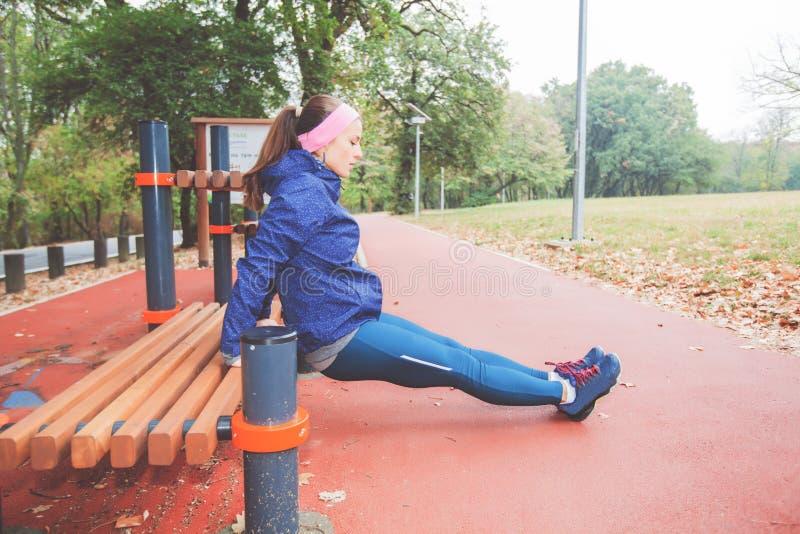 Färdig ung kvinna som gör konditionövningsSitta-UPS den utomhus- genomköraren royaltyfria bilder