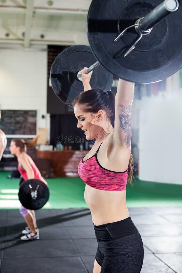 Färdig ung kvinnlig lyftande skivstång i konditionmitt arkivfoton