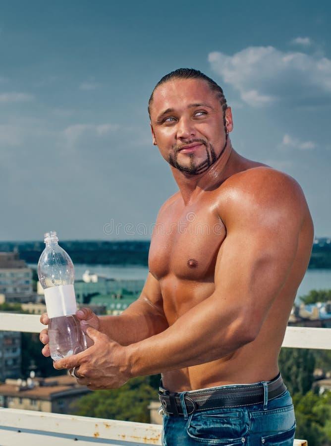 Färdig ung man med dricksvatten arkivfoto
