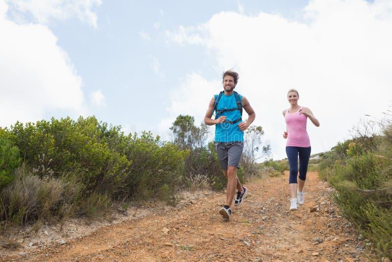 Färdiga attraktiva par som joggar ner bergslinga arkivfoton
