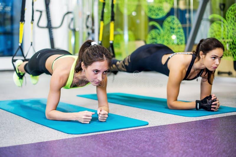 Färdiga flickor i idrottshallen som gör plankan, övar för baksida royaltyfria foton