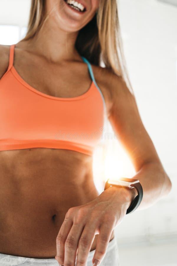 Färdiga kvinnablickar på den smarta klockan och räkningar spenderade upp kalorier, når de har utbildat i solig idrottshall sunt b royaltyfri fotografi