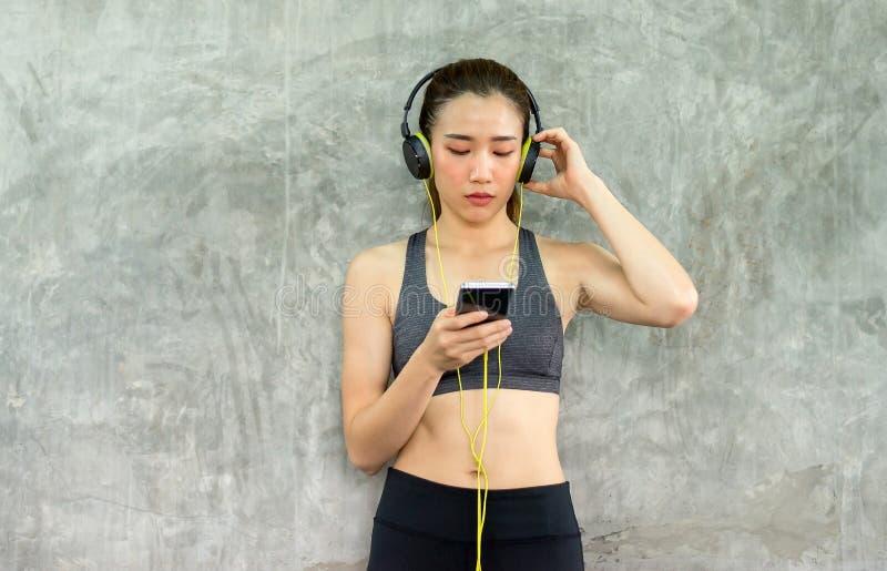 Färdiga kvinnor som använder den smarta telefonanslutningsinternet med headphonen och lyssnar till musik, medan sitta med, koppla fotografering för bildbyråer
