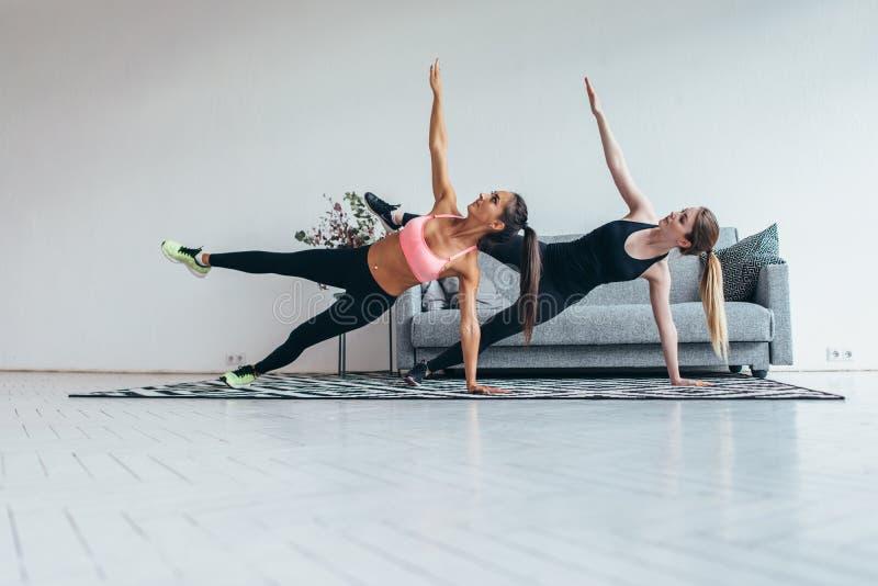 Färdiga kvinnor som gör sidoplankan, övar praktiserande pilates hemma royaltyfri bild