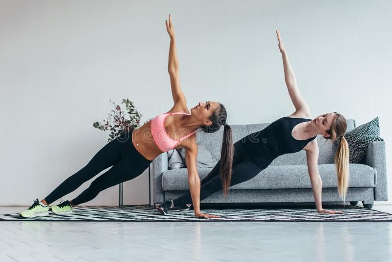 Färdiga kvinnor som gör sidoplankan, övar praktiserande pilates hemma fotografering för bildbyråer