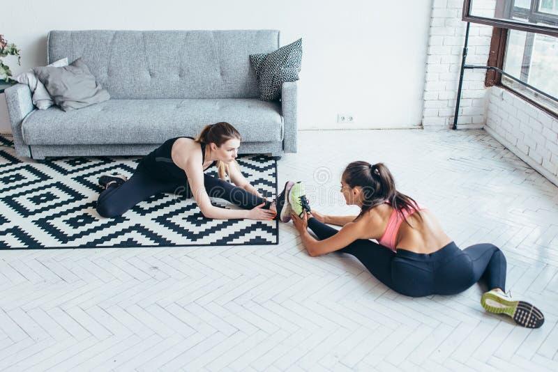 Färdiga kvinnor som gör sträckning, medan sitta på golvet hemma royaltyfri fotografi