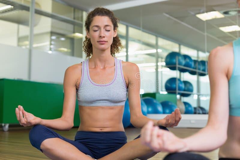 Färdiga kvinnor som tillsammans gör yoga i studio royaltyfria bilder