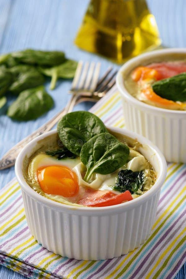 Färdiga matägg bakade med spenat och tomater royaltyfri fotografi