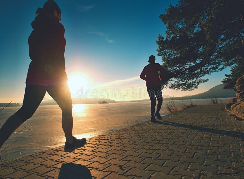 Färdiga par, man och kvinna som kör längs strand arkivfoto