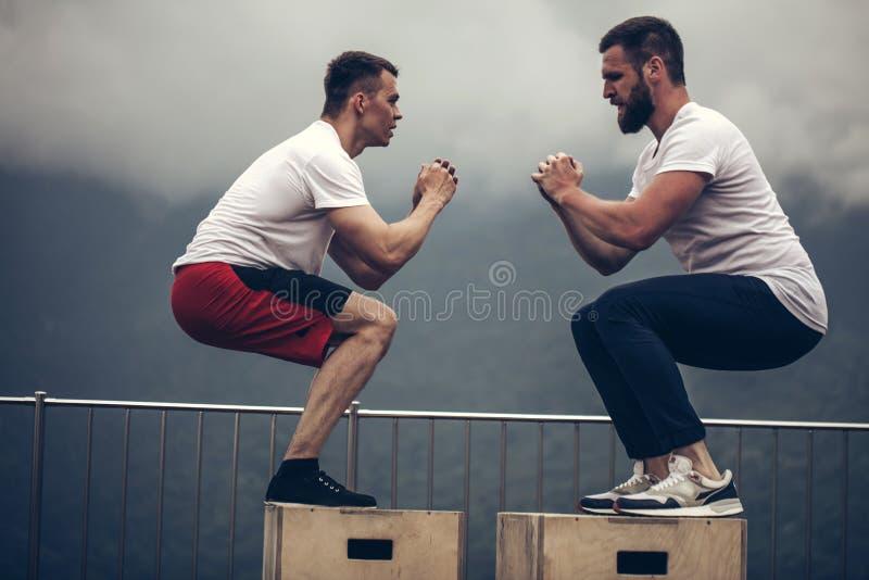 Färdiga unga idrottsmän som överst gör askhopp som en grupp som är utomhus- av berget royaltyfria foton