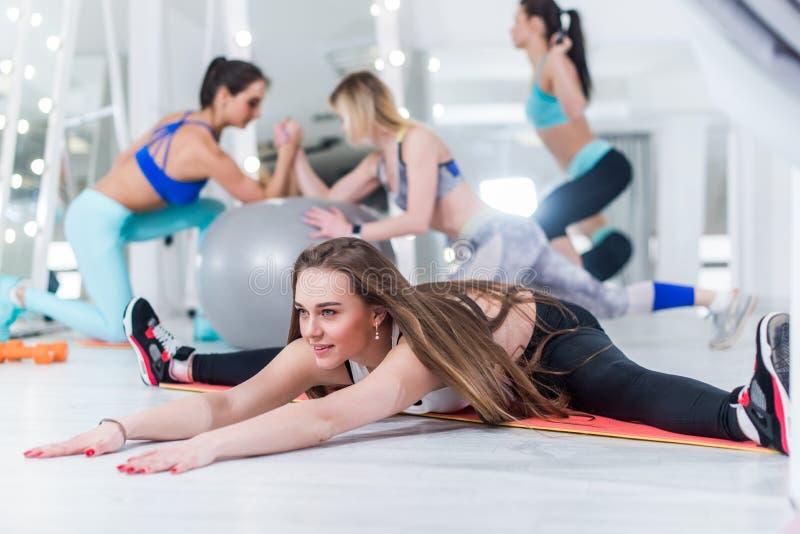 Färdiga unga kvinnor som utarbetar i idrottshall med att le unga flickan i fokusen som gör fullt kluvet lutande framåt arkivbild