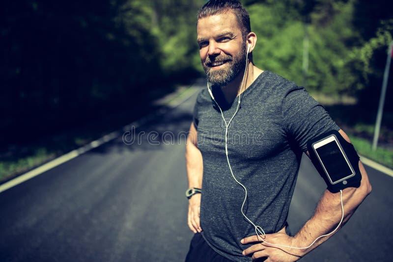 Färdigt anseende för ung man på en landsväg, medan jogga royaltyfri fotografi