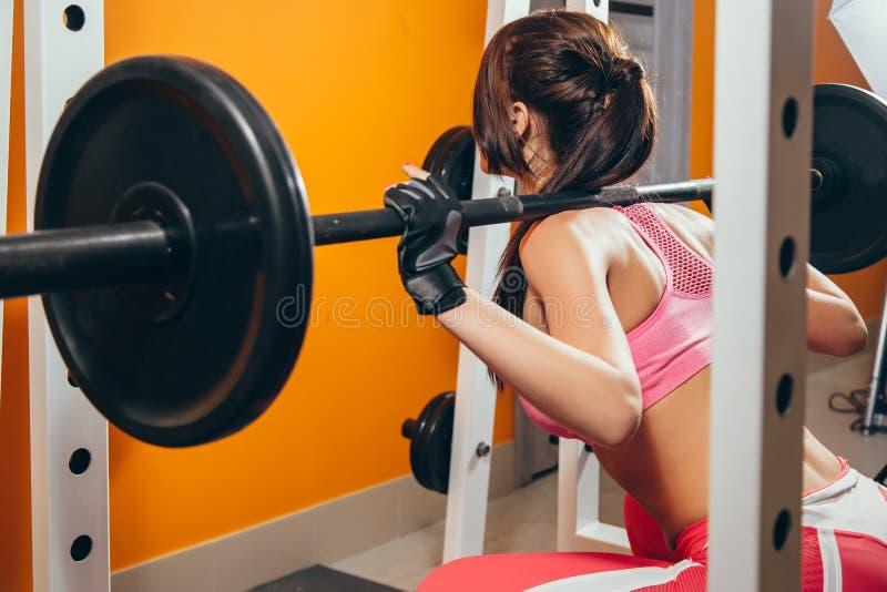 Färdigt göra för kvinna som är satt med skivstången i idrottshallen fotografering för bildbyråer