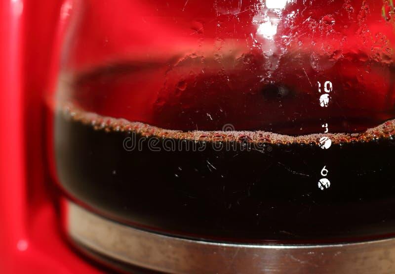 Färdigt kaffe i en glasburk, berett av en kaffebryggare Det är praktiskt att hålla kaffet varmt arkivbild