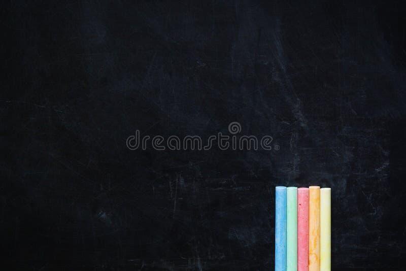 Färg chalks på svart brädebakgrund arkivbild