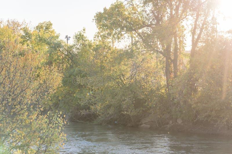 Färg för nedgånglövverk på flodstranden parkerar och blå himmel I för solnedgångmoln arkivfoton