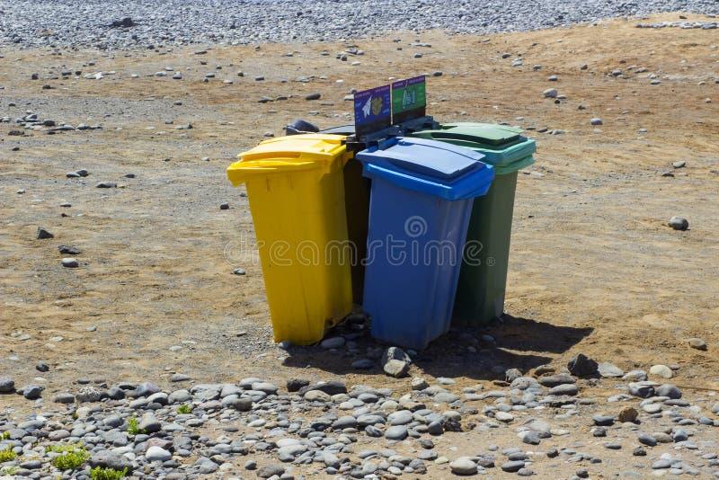 Färg kodifierad rubbishe slänga i soptunnan för återanvändning av avfalls på en solig strand i Teneriffe i Playa Las Americas i d fotografering för bildbyråer