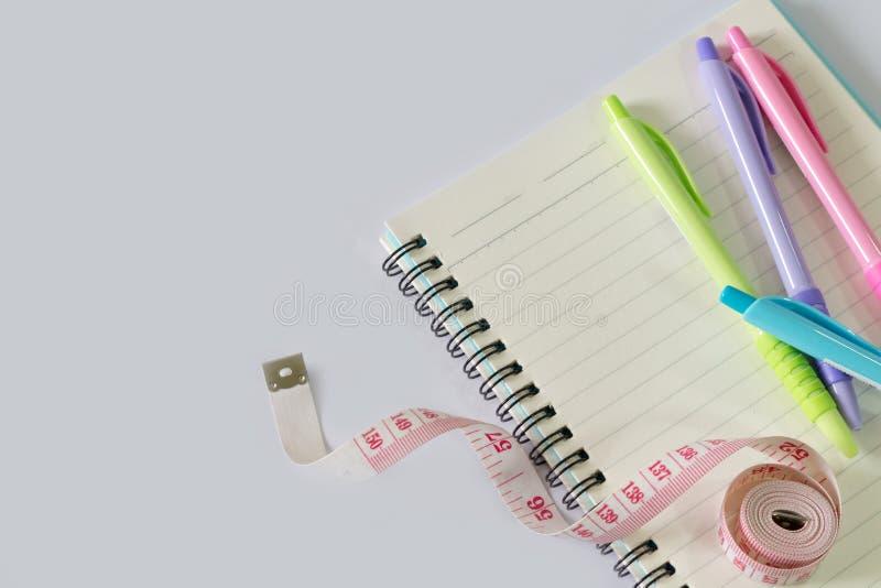 Färg skriver pålagt en anteckningsbok, och det finns en mäta linje Alla lade på det vita golvet/färgpennor är rosa, gröna, blåa o royaltyfria foton