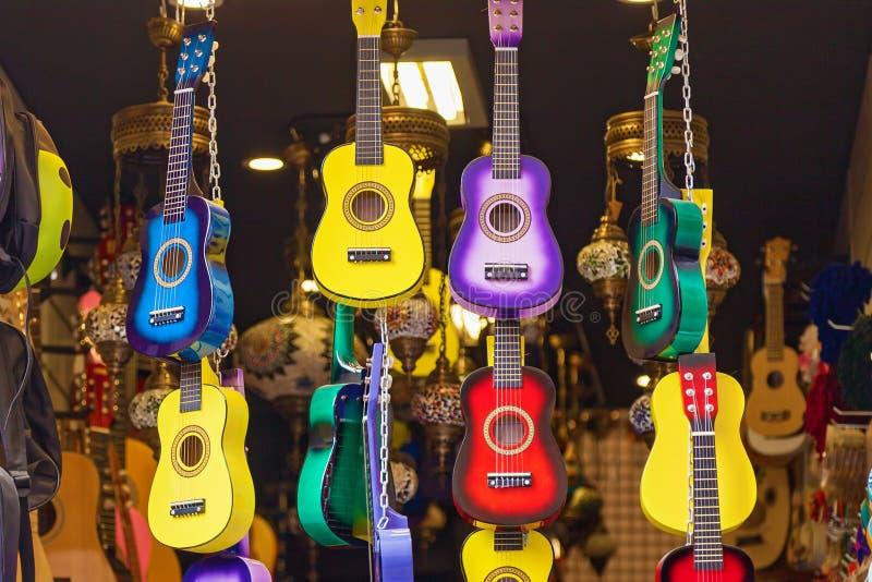 Färga gitarrer hänger i butiken royaltyfria foton