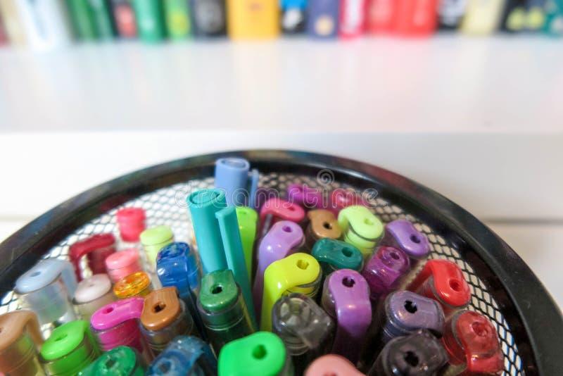 Färga pennor i ingreppsbehållare mot den suddiga bokhyllan fotografering för bildbyråer