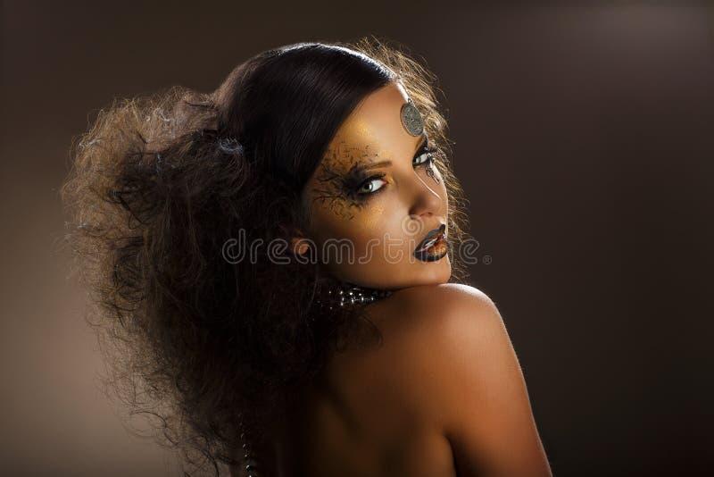 Färga. Stiliserad kvinnas framsida med guld- smink. Idérik modern kroppkonst arkivbild