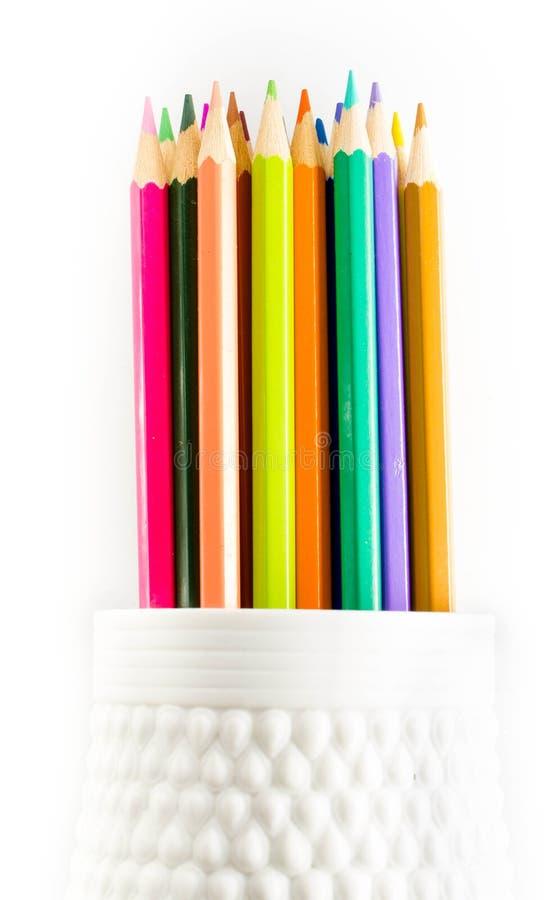 Färgad grupp av blyertspennor i tillförsel för en koppskola på vita lodisar royaltyfri foto