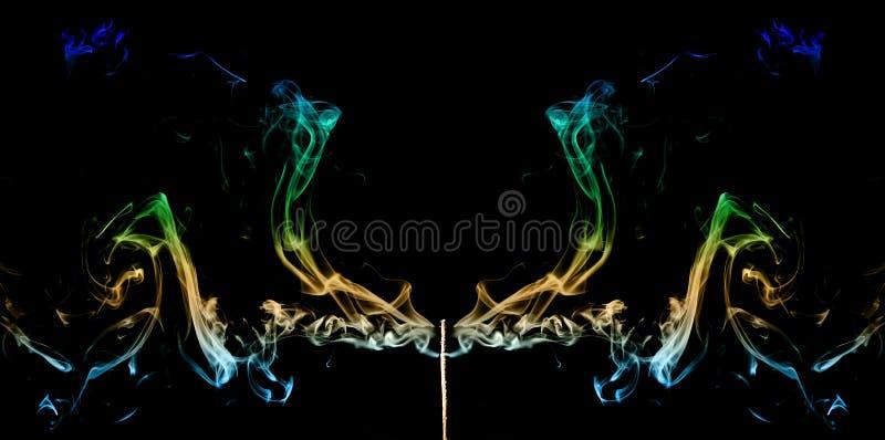 Färgad rök som kommer ut ur rökelsepinnar abstrakt konströk arkivfoto