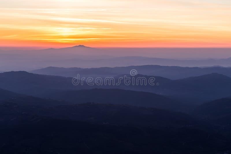 Färgade Beautifully himmel på solnedgången, med berglager och mist dem emellan arkivbilder
