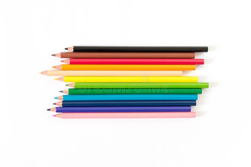 Färgade blyertspennor förläggas i horisontalrader På en vit bakgrund royaltyfria foton