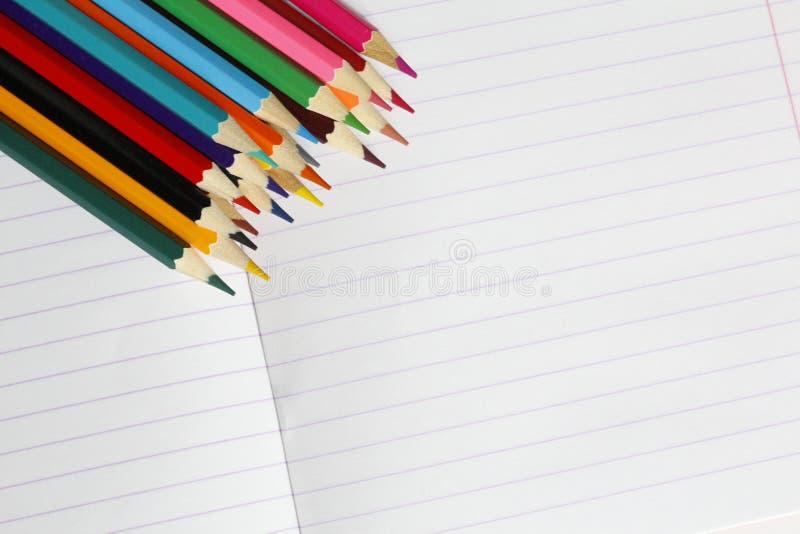 Färgade blyertspennor ligger på en randig anteckningsbok Det finns ett st?lle f?r text royaltyfria bilder