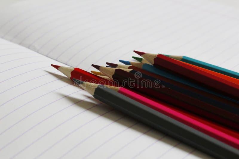 Färgade blyertspennor ligger på en randig anteckningsbok Det finns ett st?lle f?r text royaltyfri bild