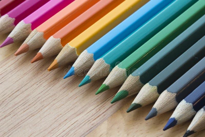 Färgade blyertspennor mot en träbakgrund arkivbilder