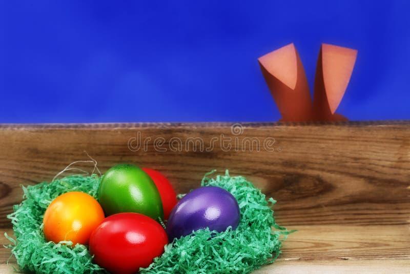 Färgade easter ägg på ett bräde, gömd easter kanin royaltyfri bild