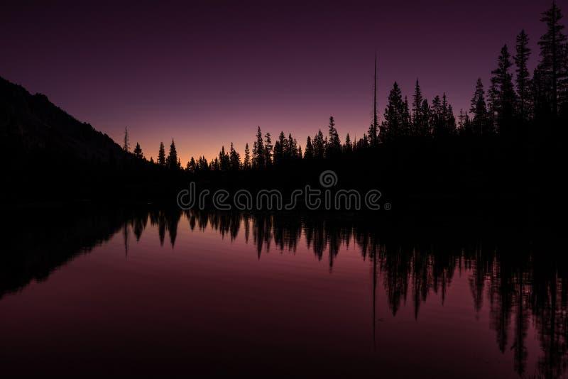 Färgade första ljus för den Idaho bergsjön himmel och reflexion royaltyfri bild