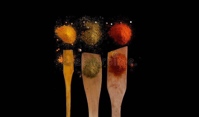 Färgade kryddor på svart bord arkivbilder