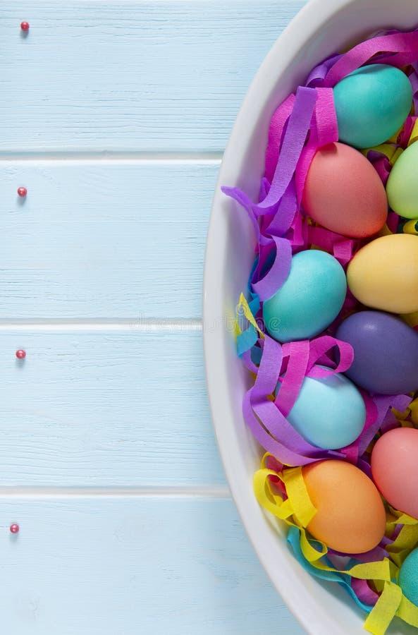 Färgade påskägg i en maträtt med färgrika pappers- band och socker strilar konfektprickar royaltyfri foto