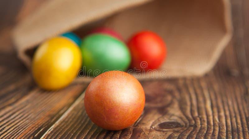 Färgade påskägg på en träbakgrund i säckväv med suddig bakgrund, närbild arkivfoton