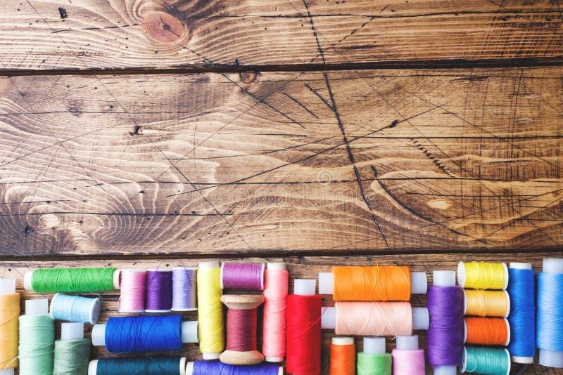 Färgade rullar av tråden som läggas ut i rader på träbakgrund kopiera avstånd royaltyfria bilder