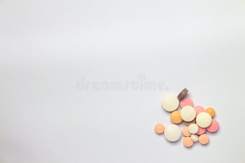 Färgade tabletter på vit bakgrund Begreppet missbruk av läkemedel arkivbild