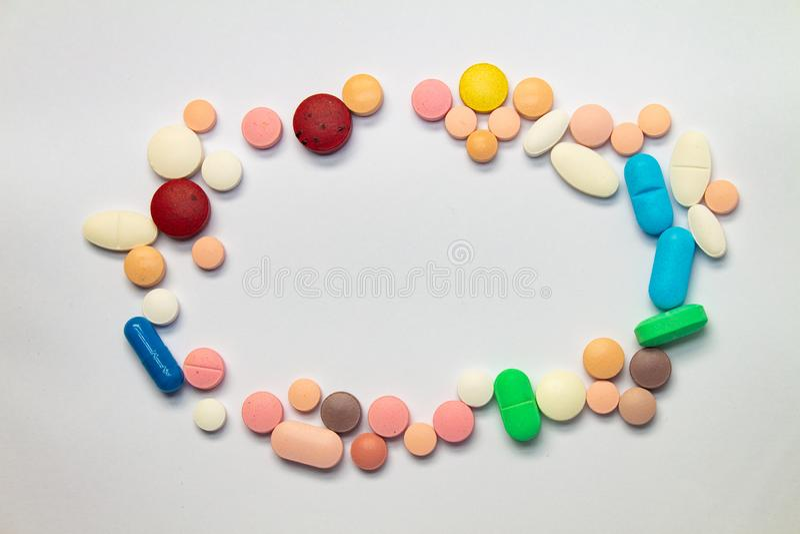 Färgade tabletter som bildar en cirkel på vit bakgrund Begreppet missbruk av läkemedel Läkemedel för lagligt bruk royaltyfri fotografi