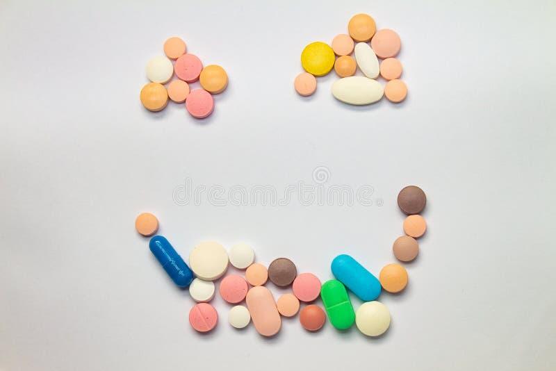 Färgade tabletter som bildar ett lyckligt ansikte mot vit bakgrund Begreppet missbruk av läkemedel Läkemedel för lagligt bruk royaltyfri fotografi